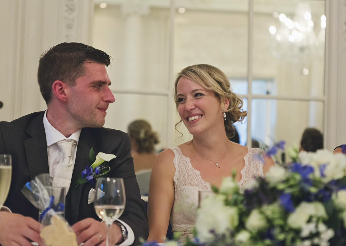 A bride and groom smiling at each other while sat at their wedding reception