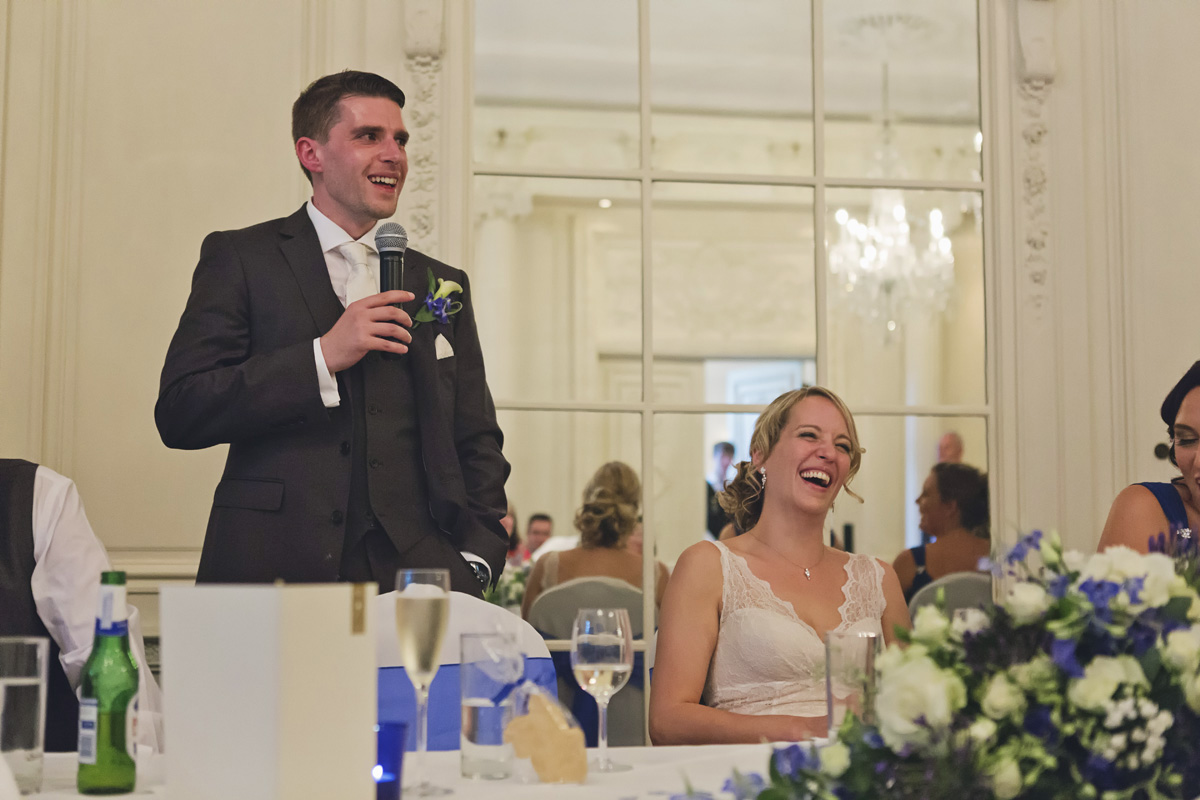 A bride laughing as her husband gives his wedding speech