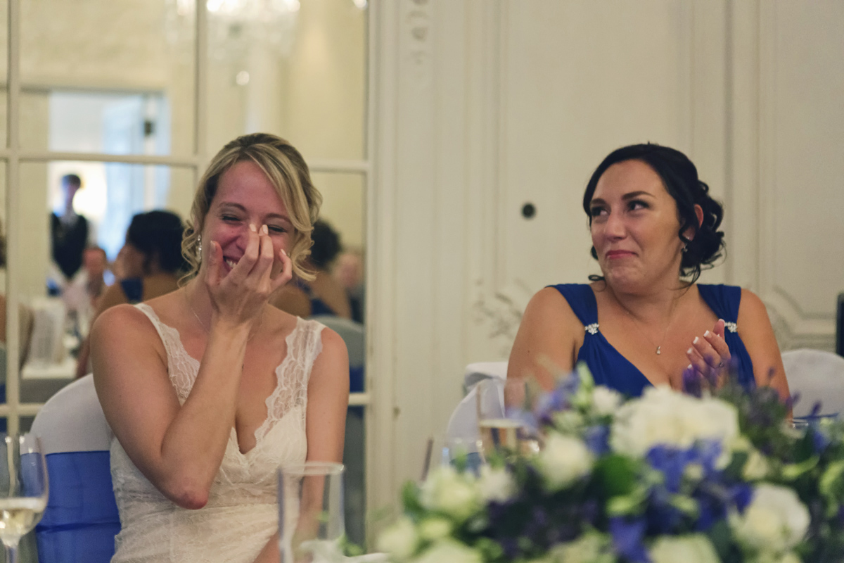 A bride and her bridesmaid wipe away tears during the speeches at a wedding