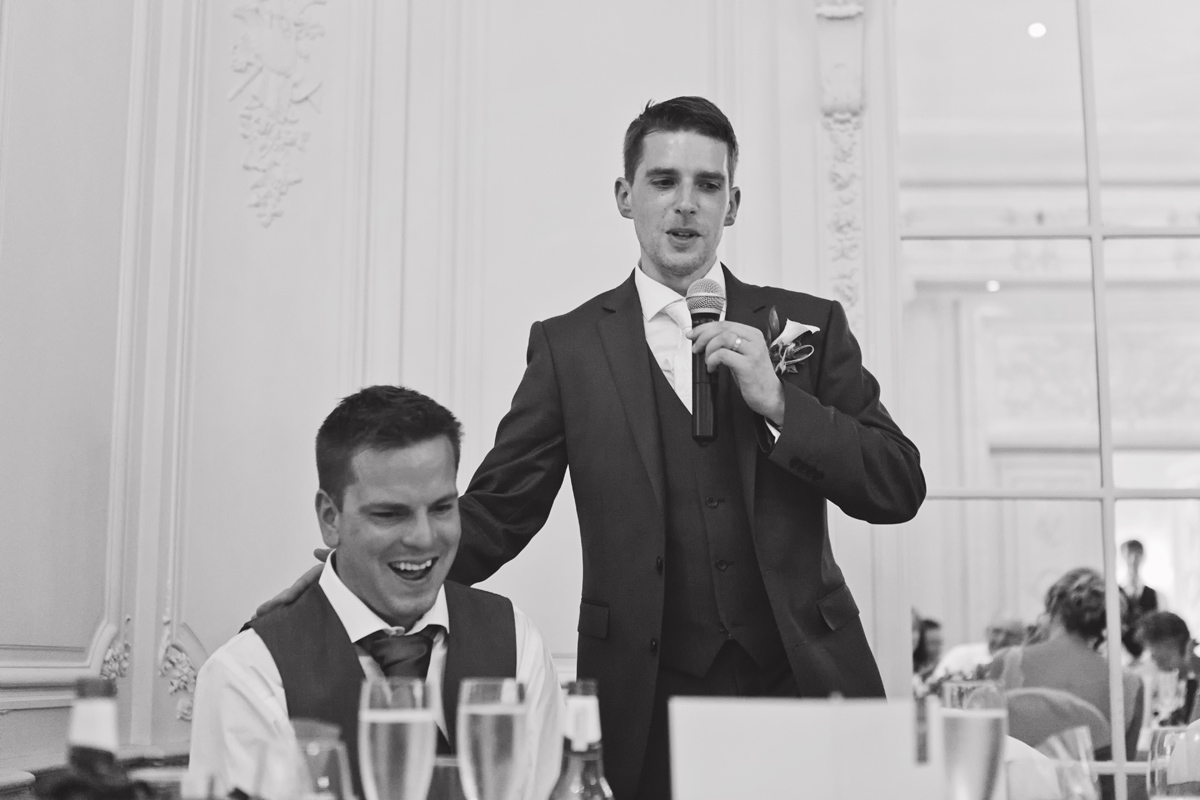A groom pats his best man on the back during his speech at a wedding reception