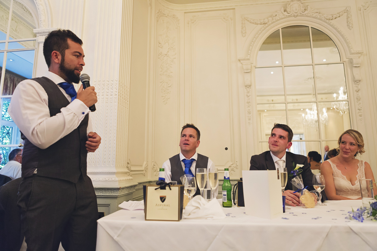 A groomsman gives a speech at a wedding reception as the bride, groom & best man look on