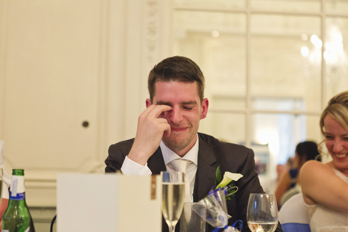 A groom looking embarrassed during the speeches at his wedding