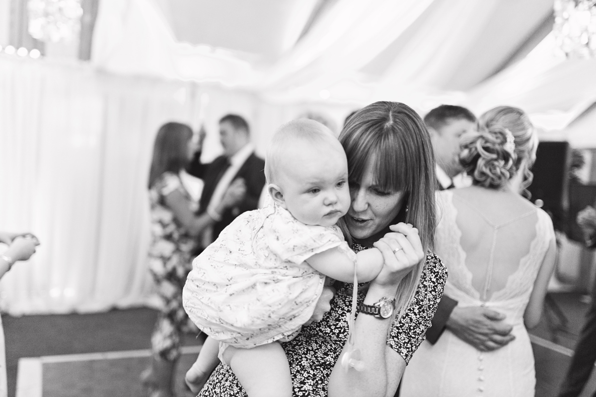 A mother dances along with her young baby at wedding reception
