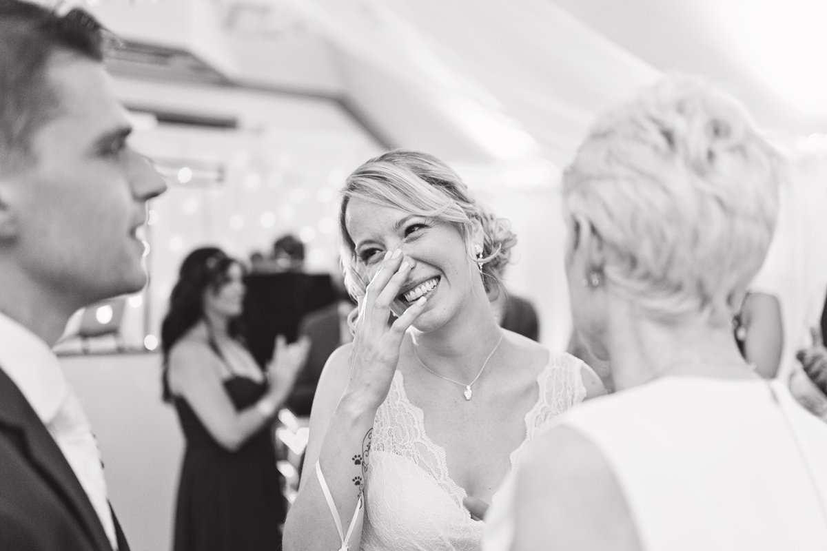 A bride laughing while chatting to guests at her wedding reception