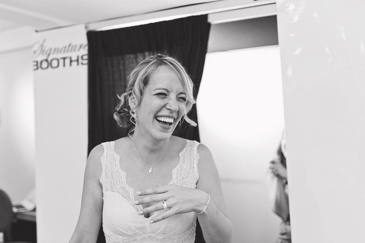 A bride laughing as she walks out of a Photo Booth at her wedding reception