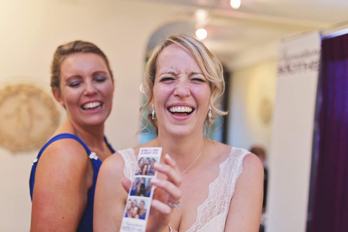 A bride and bridesmaid laughing at their photo booth photos