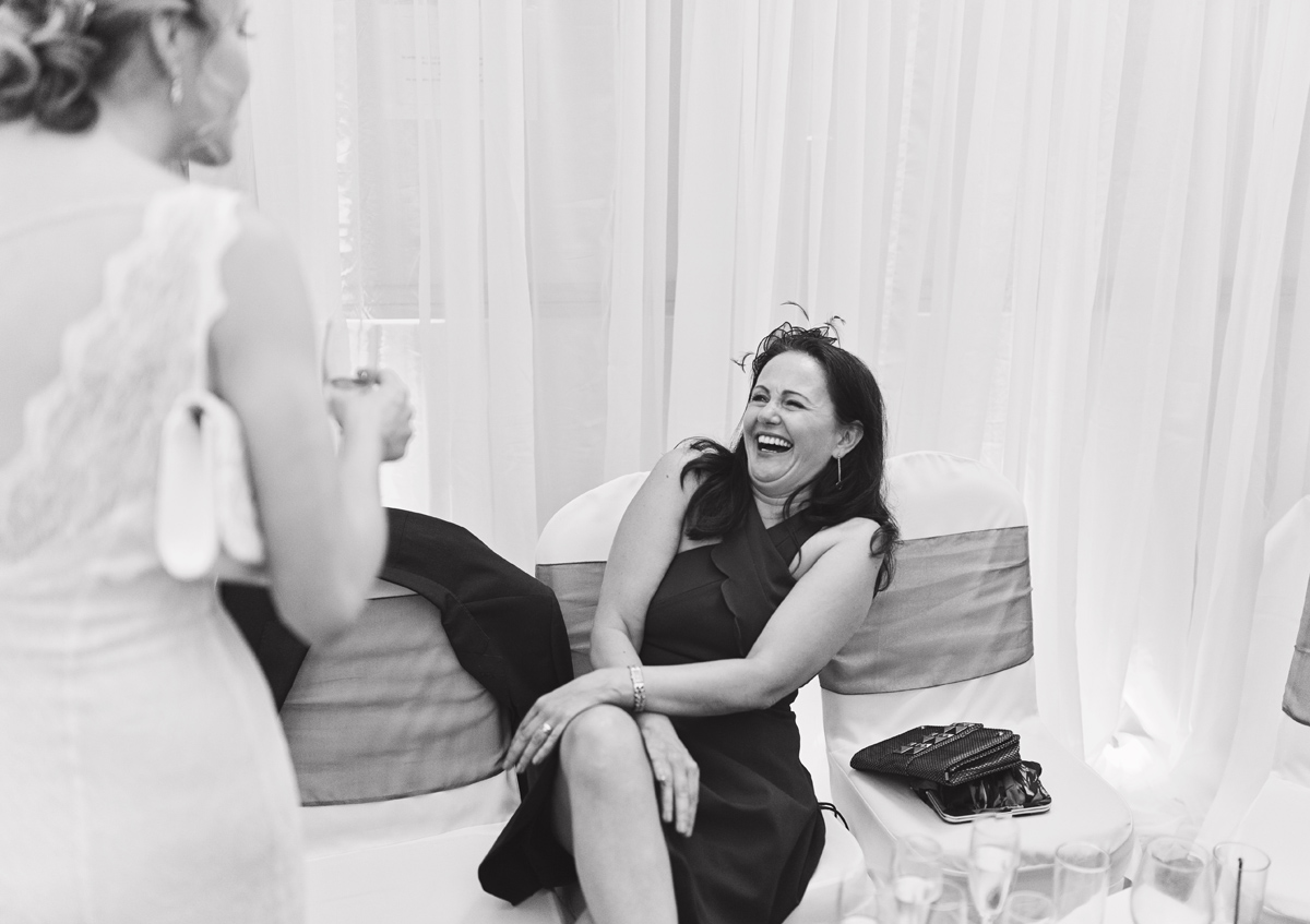 A black and white image of a wedding guest laughing at a drinks reception