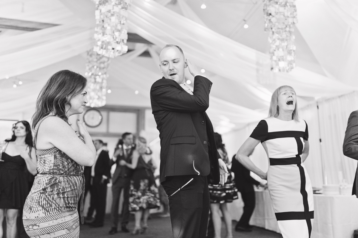 A black and white shot of wedding guests on the dance floor at a reception