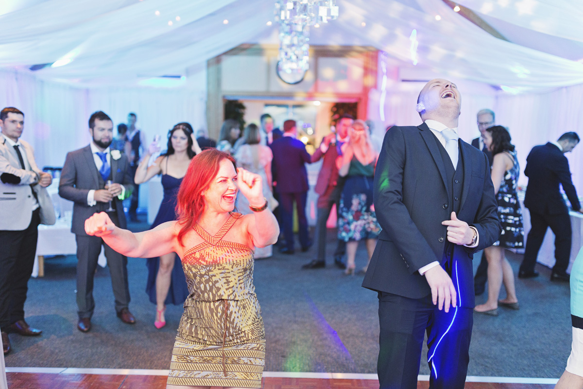 Guests laughing while dancing at a wedding reception