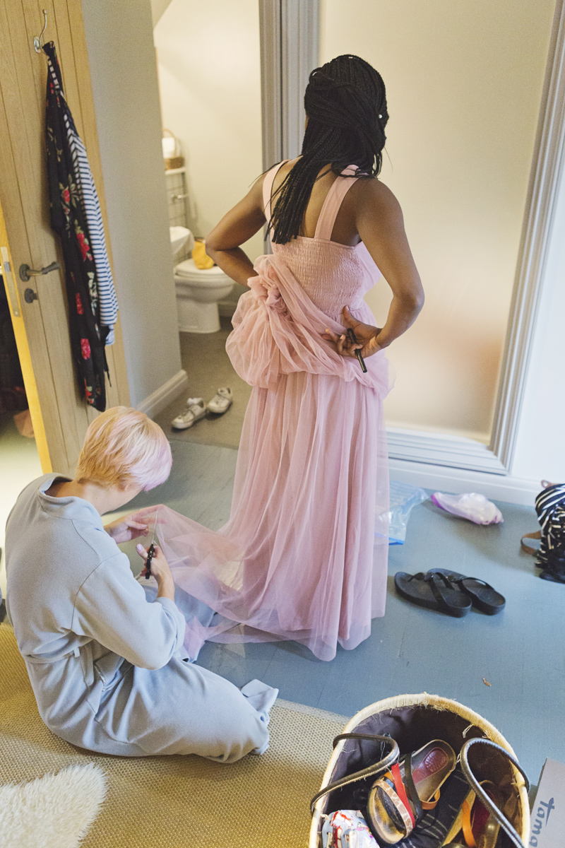 A bridesmaid has adjustments made to her dress in a hotel room