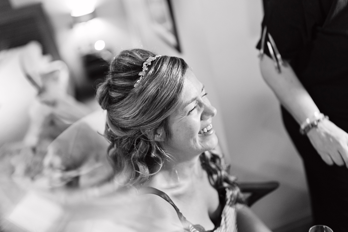 A black & white shot of a bride laughing without makeup on