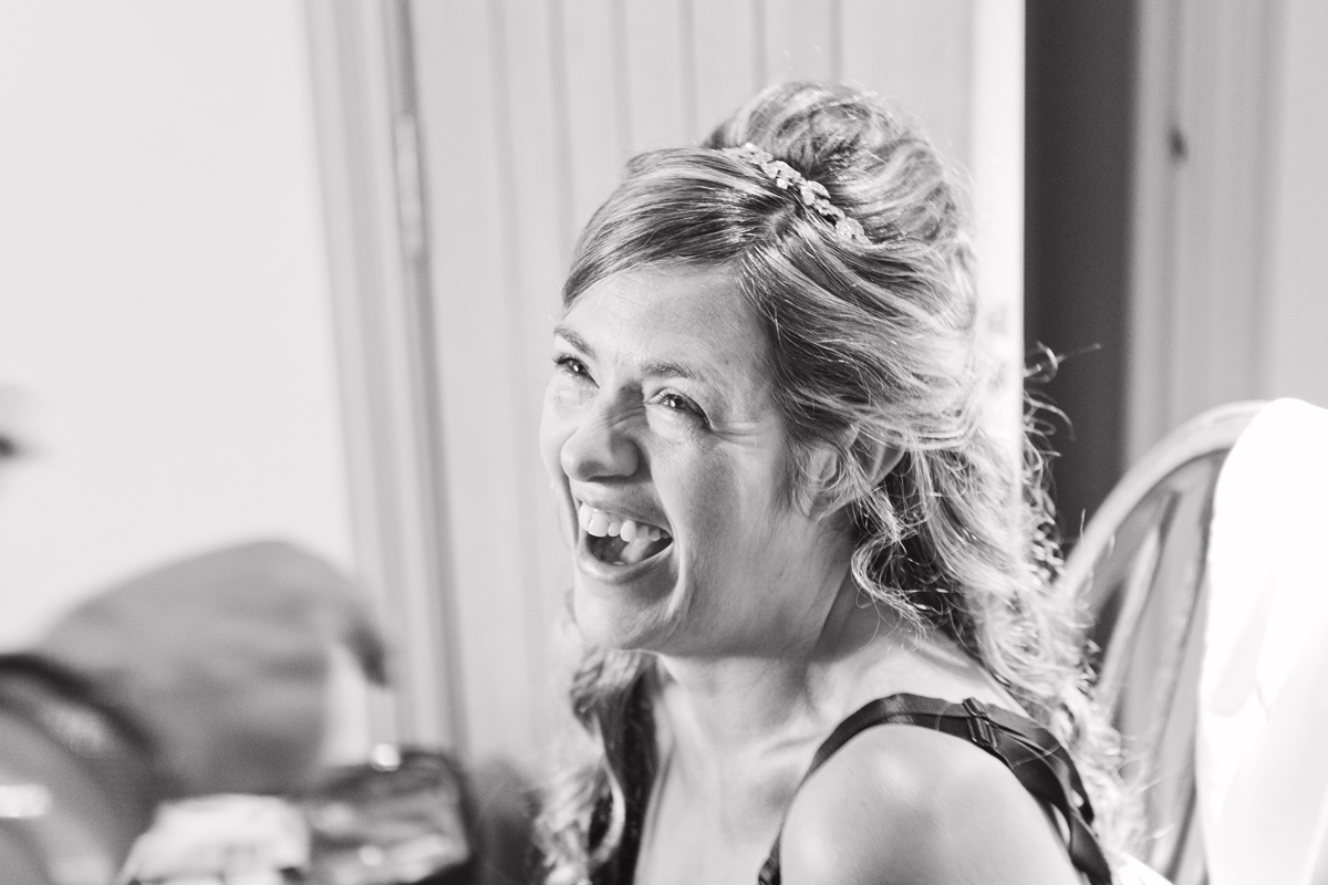 A bride to be laughing while having her make up done
