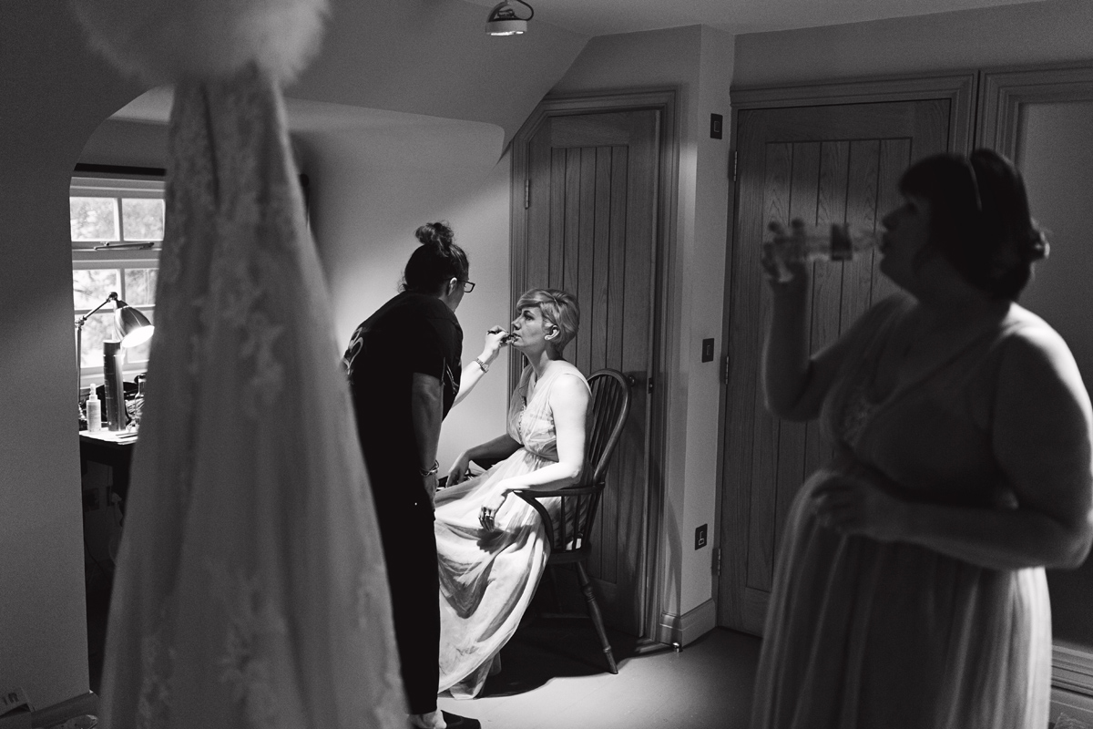 A bridesmaid has her makeup applied in a hotel room while another drinks from a bottle