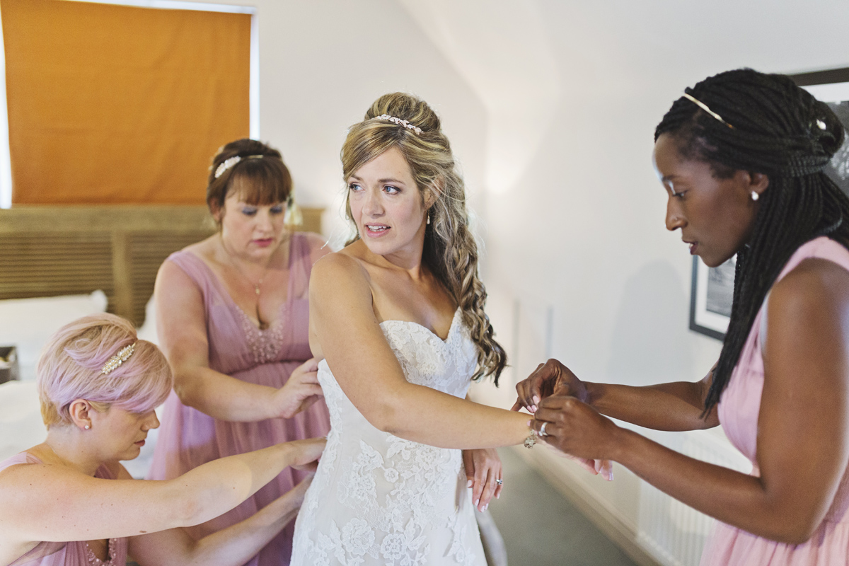A bride has her dress adjusted by her bridesmaids in a hotel room