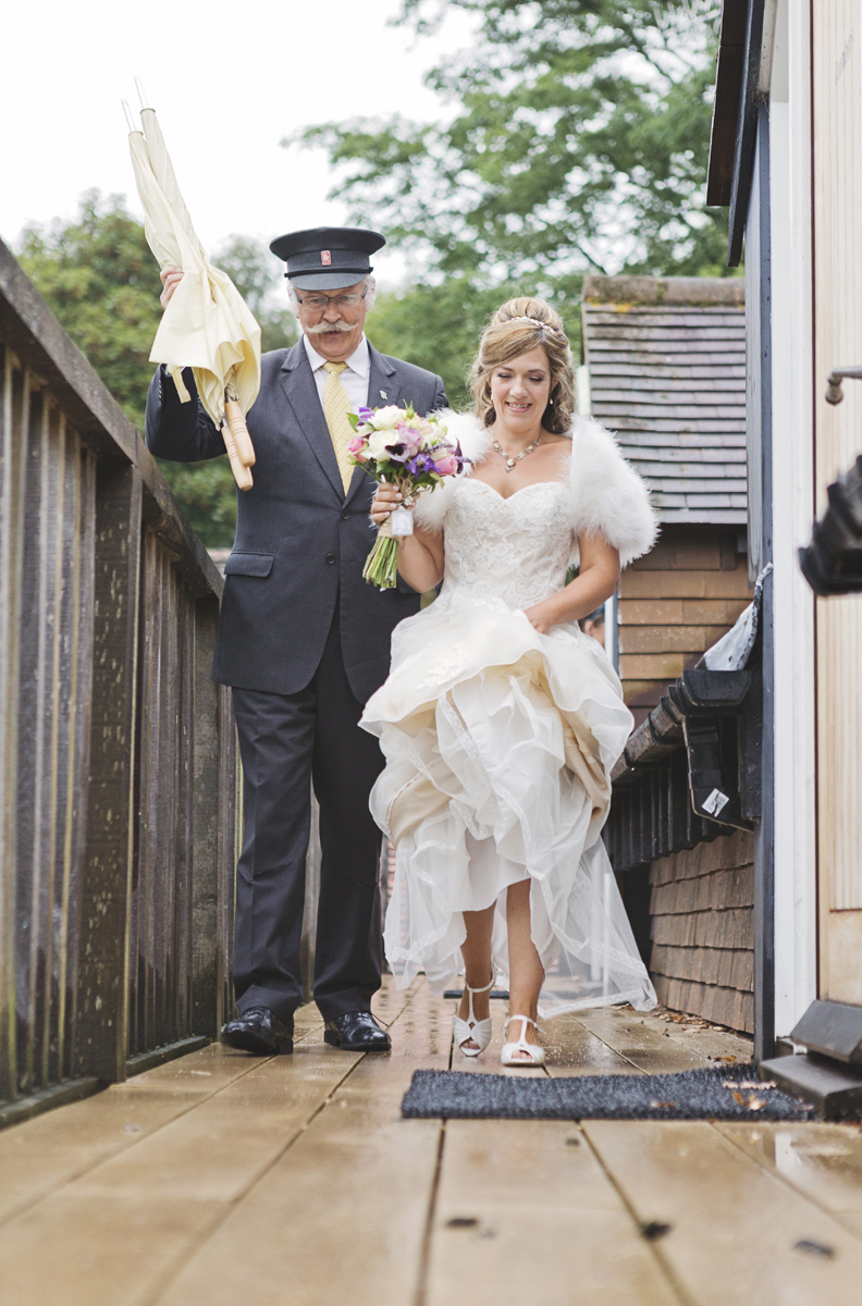A chauffeur escorts a bride to be along a walkway