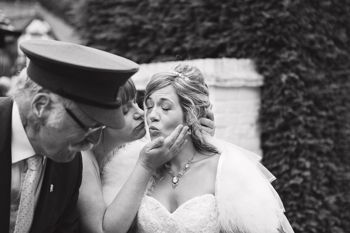 A bride gets a kiss from her bridesmaid as leaves for the ceremony