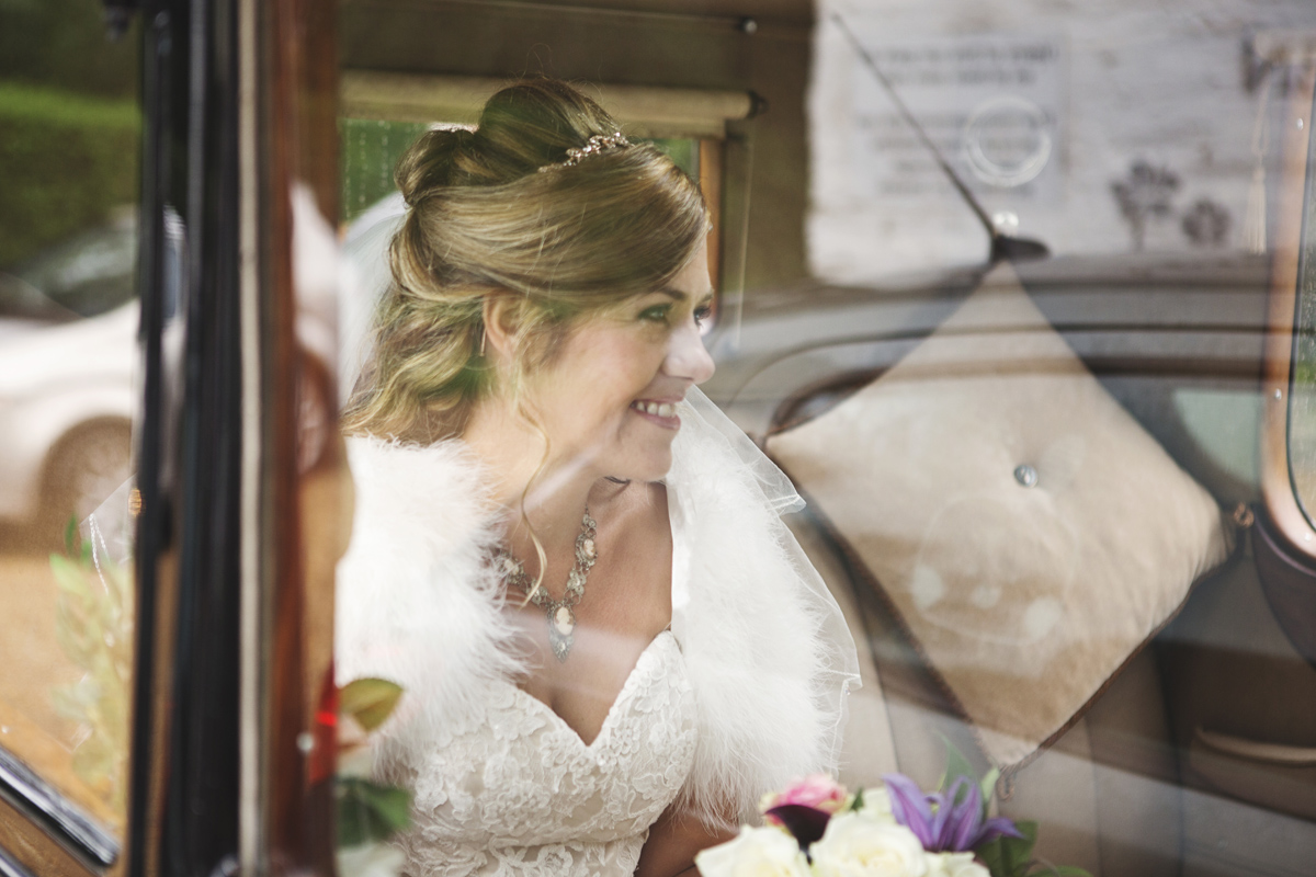 A bride smiles from inside her wedding car
