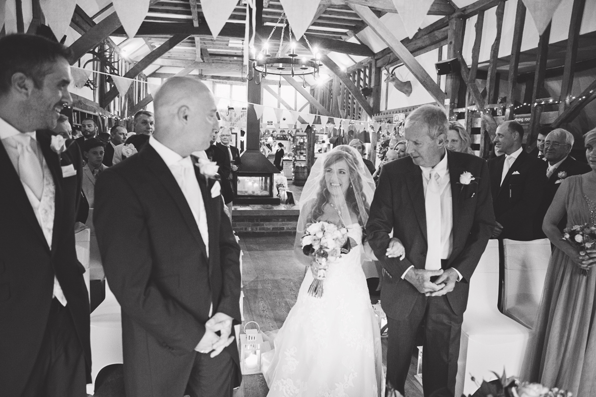 A bride & her father walk down the aisle at Red Barn Surrey