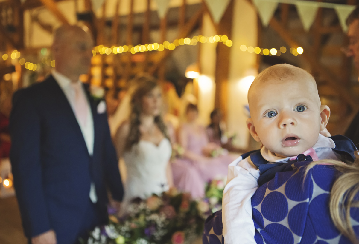 A baby looking at the camera in the foreground with a wedding couple exchanging vows in the background