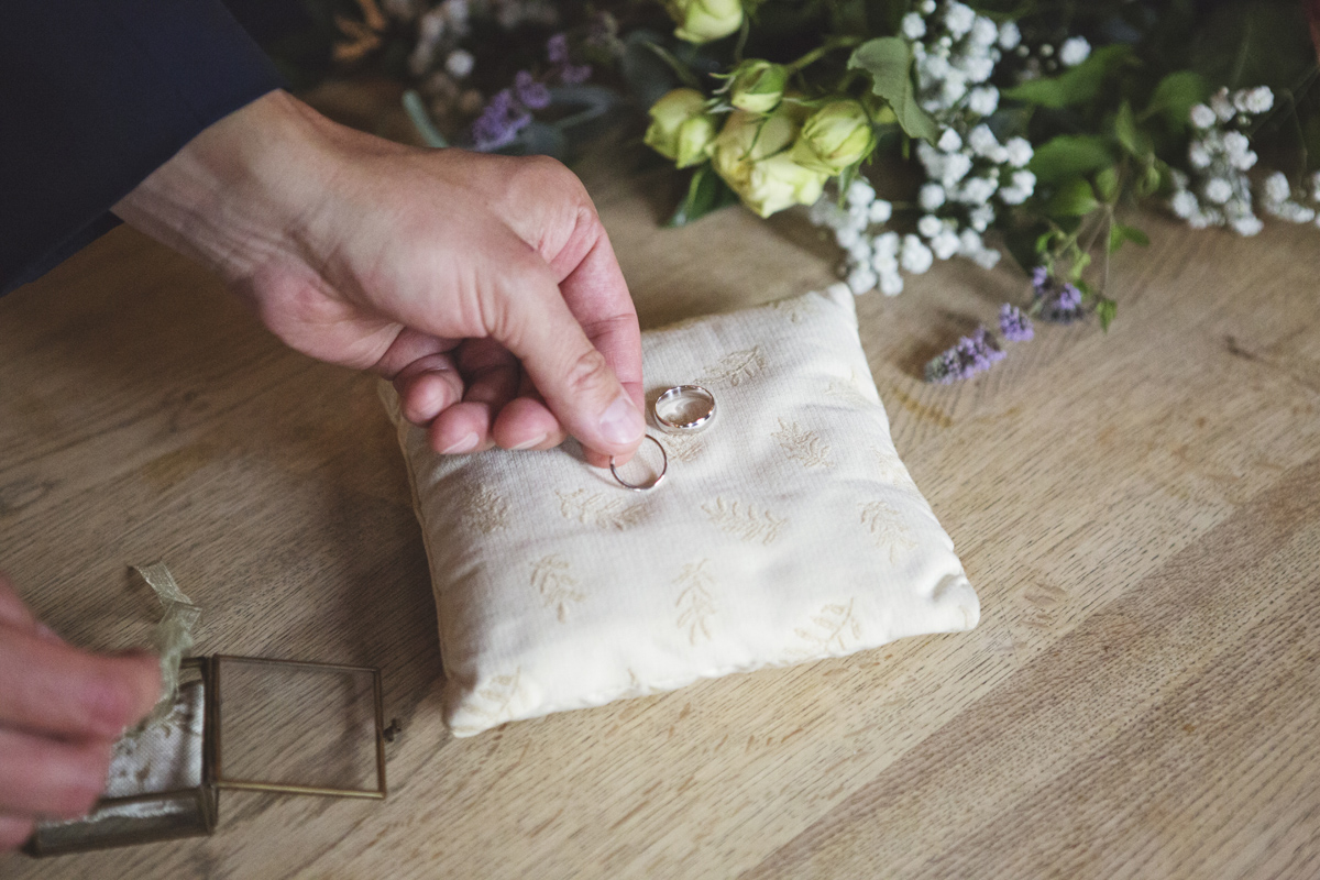 A close up shot of wedding rings being placed on a cushion during a wedding ceremony