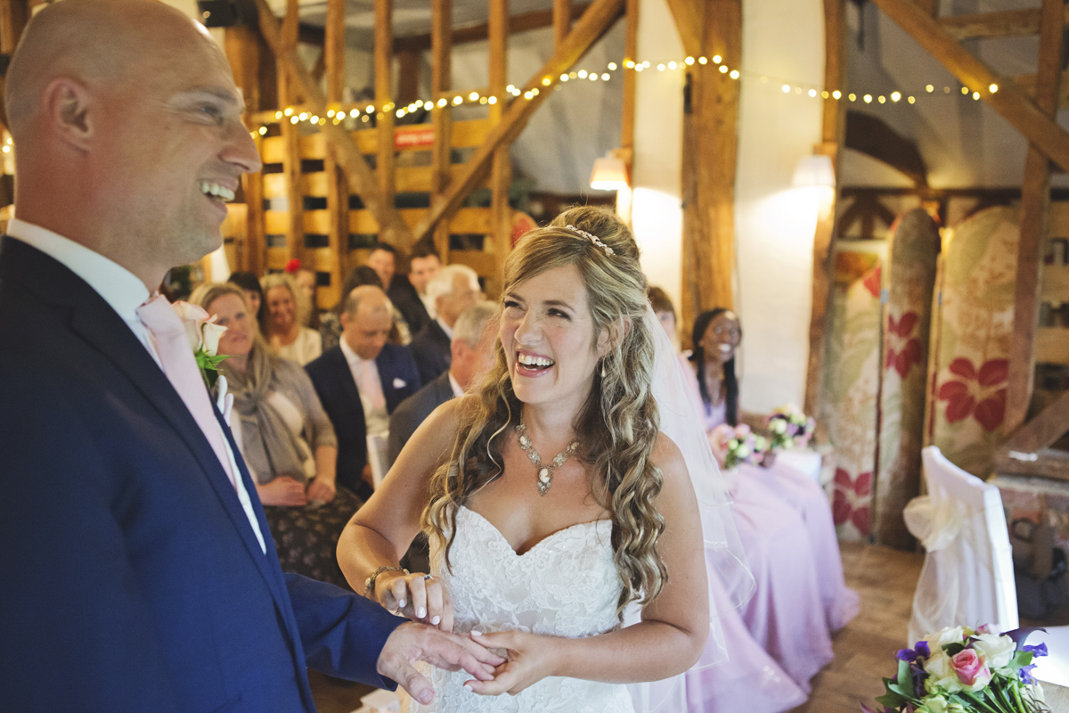 A wedding couple laughing as the bride attempts to put the ring on the Groom's finger
