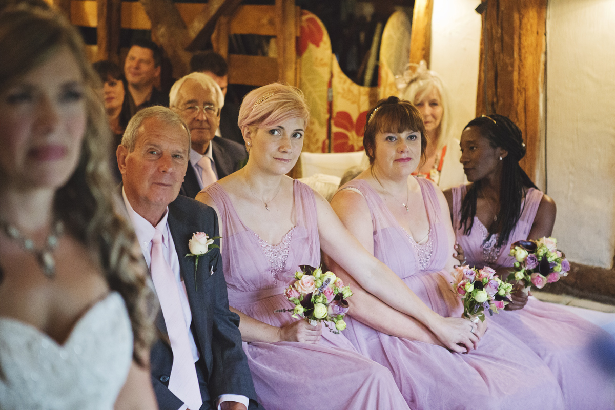 A bride's father and her bridesmaids look on as she exchanges her wedding vows