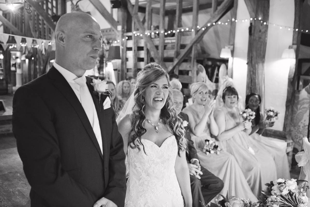 A wedding couple smile as their guests applaud at their ceremony
