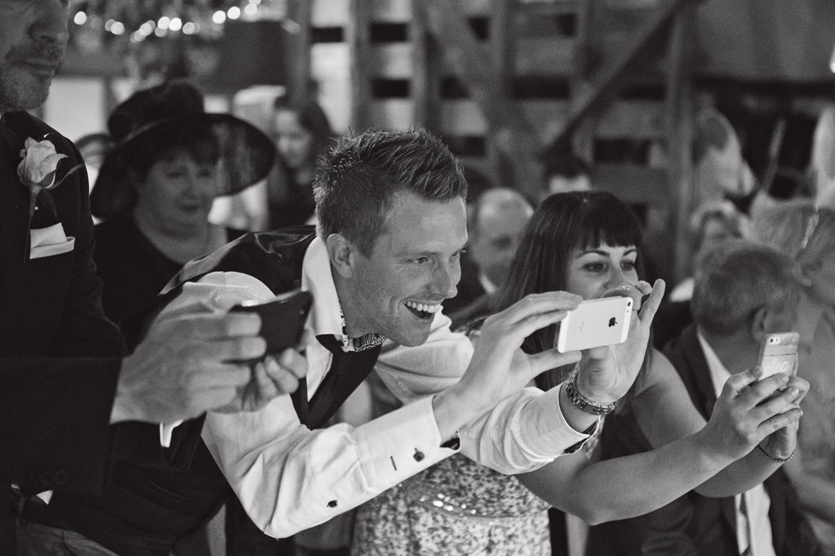 Wedding guests line up to take photos on their phones