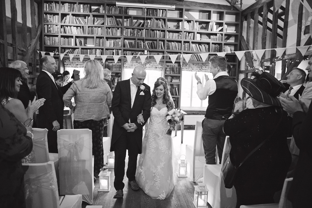 A bride & groom walk down the aisle at the Red Barn Wedding venue in Surrey