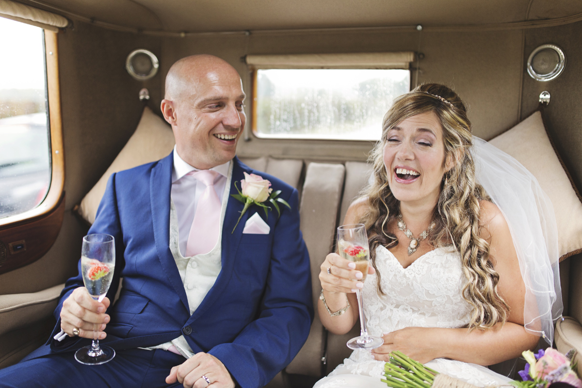 Newlyweds laughing while drinking Champagne in the back of a classic car