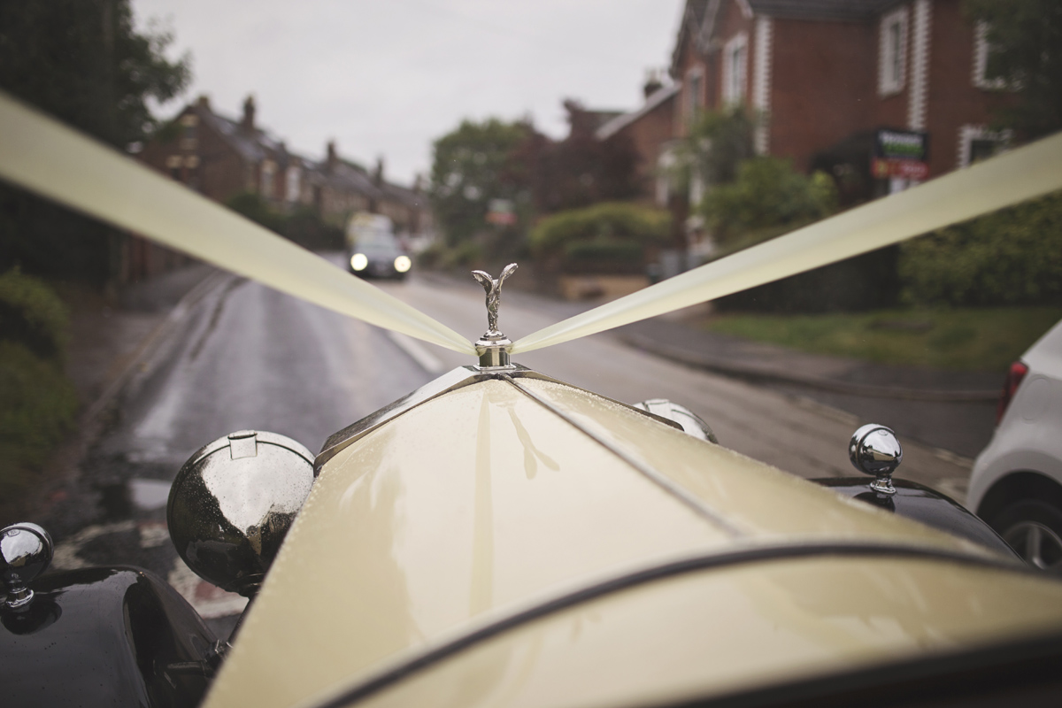 A shot through the windscreen of a Rolls Royce wedding car driving down the road
