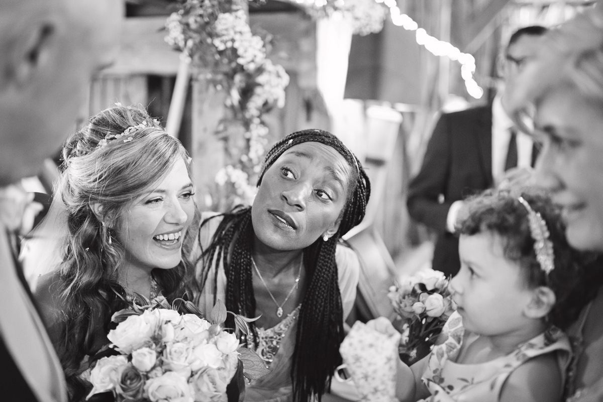 A bride & her bridesmaid chat with wedding guests