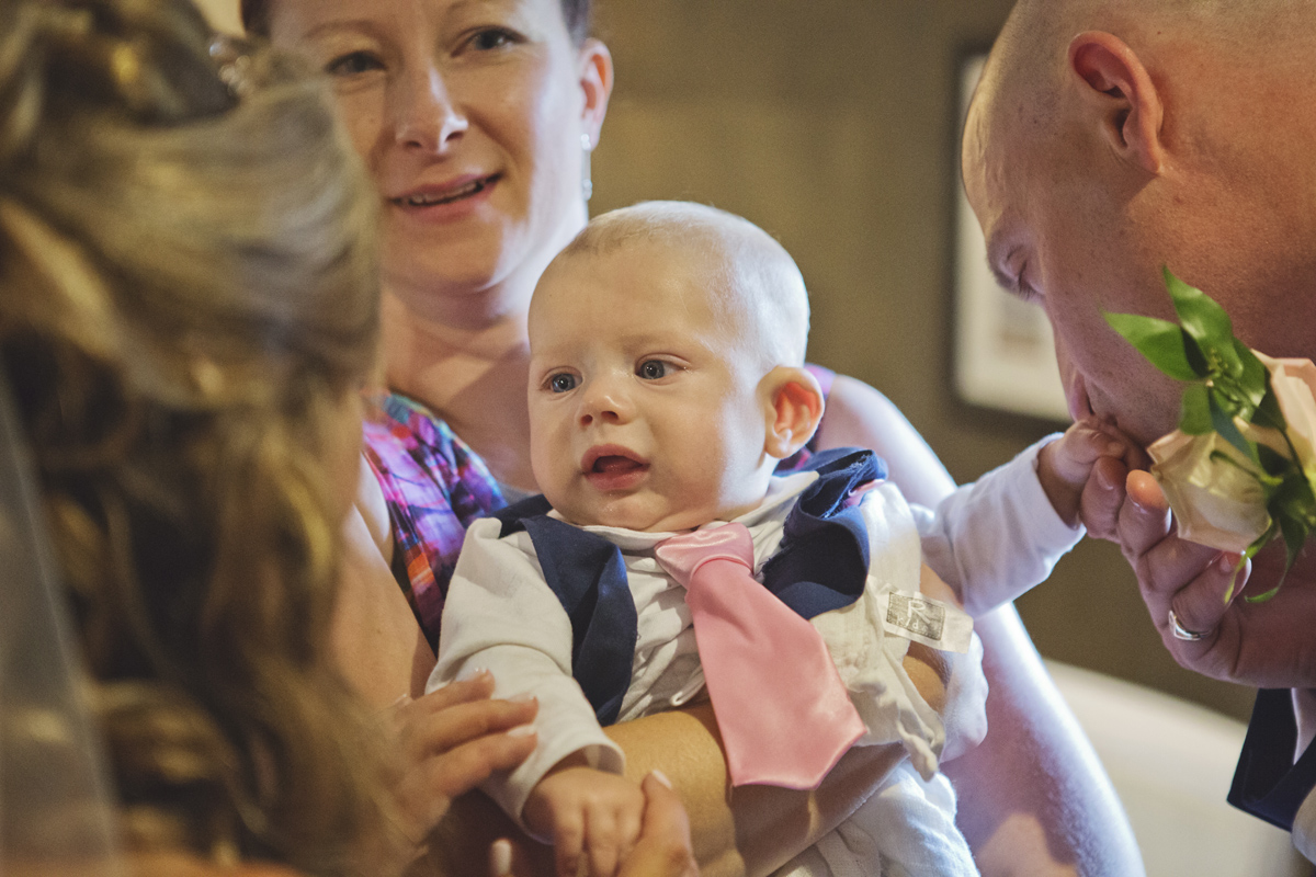 A baby is cuddled at a wedding