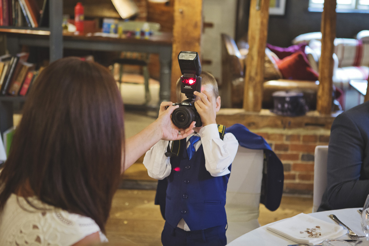 A young boy attempts to take a picture with a DSLR at a wedding reception