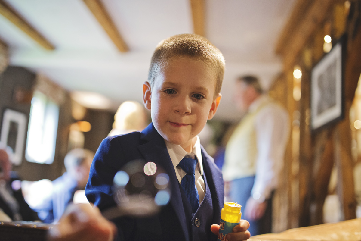A boy plays with bubbles at a wedding reception
