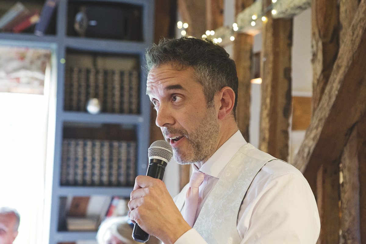 The Best Man holds a microphone while giving his speech at a wedding reception