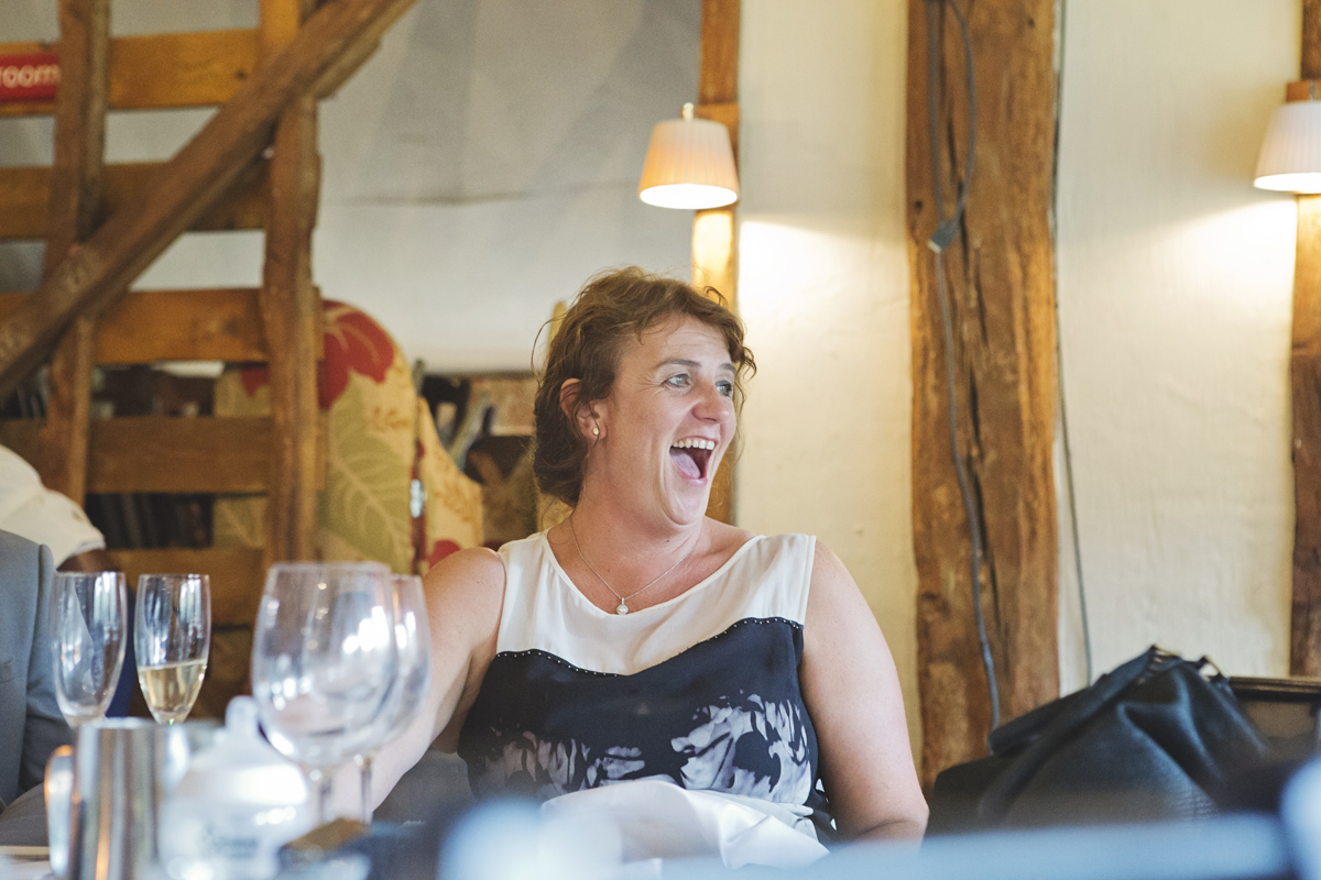 A wedding guest laughing out loud at the speeches