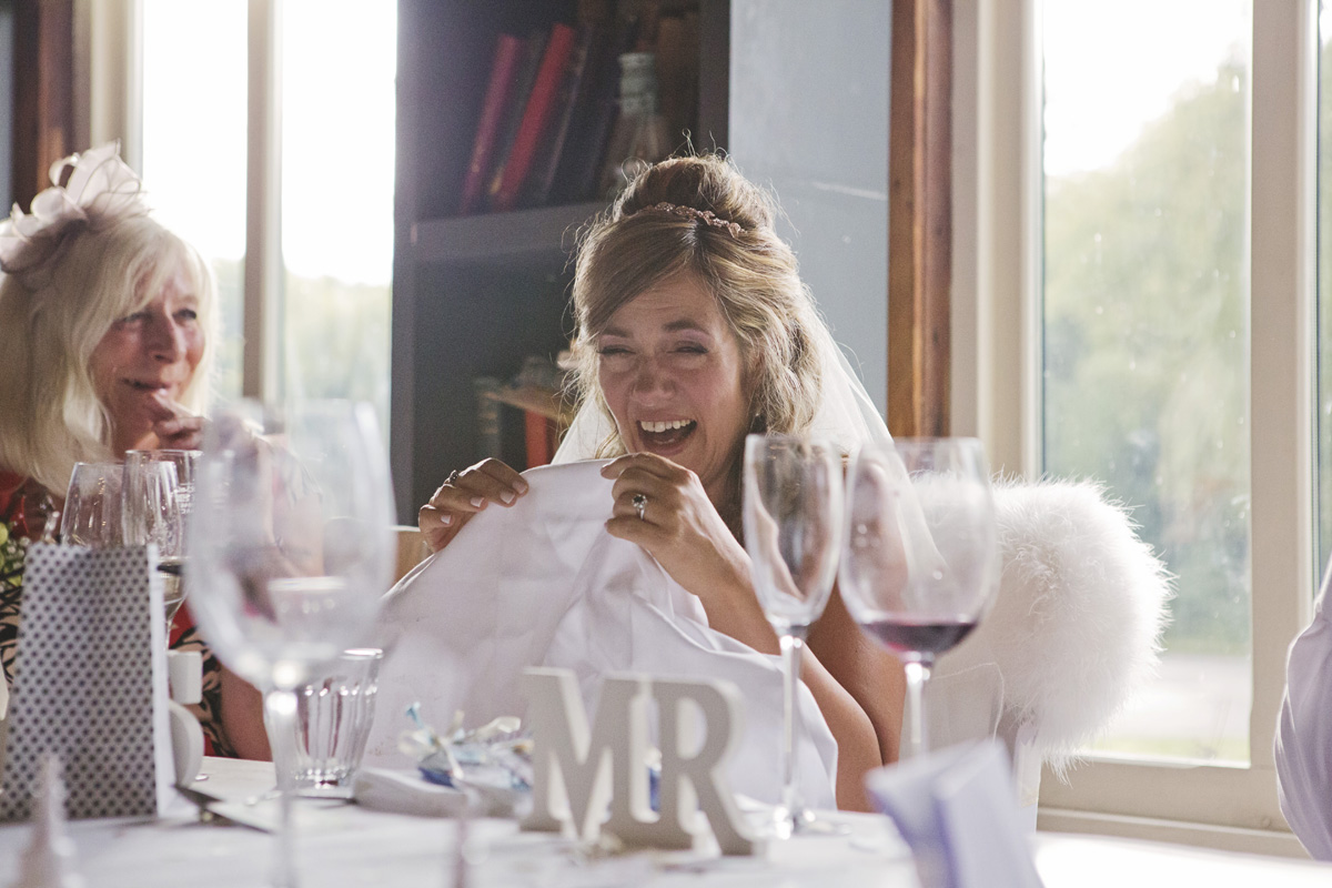 A bride sheds tears of laughter during the speeches at her wedding