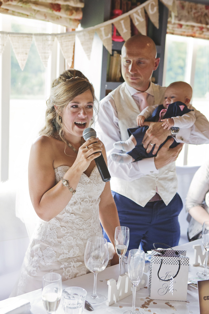 A bride gives a speech while her new husband cradles their baby at their wedding reception