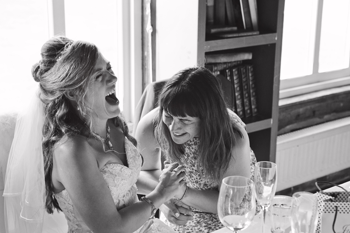 A bride and her guest share a joke at her wedding reception