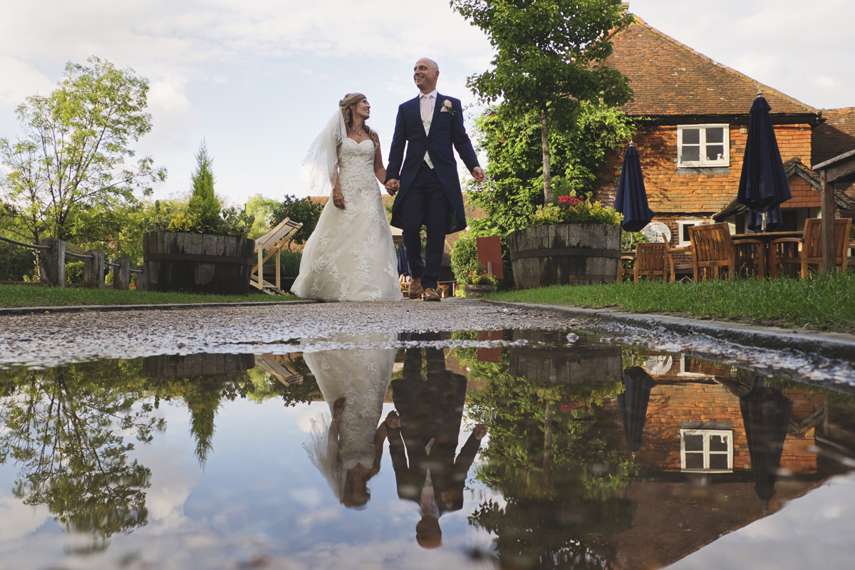 Newlyweds take a stroll with their reflections in a puddle at The Red Barn in Surrey