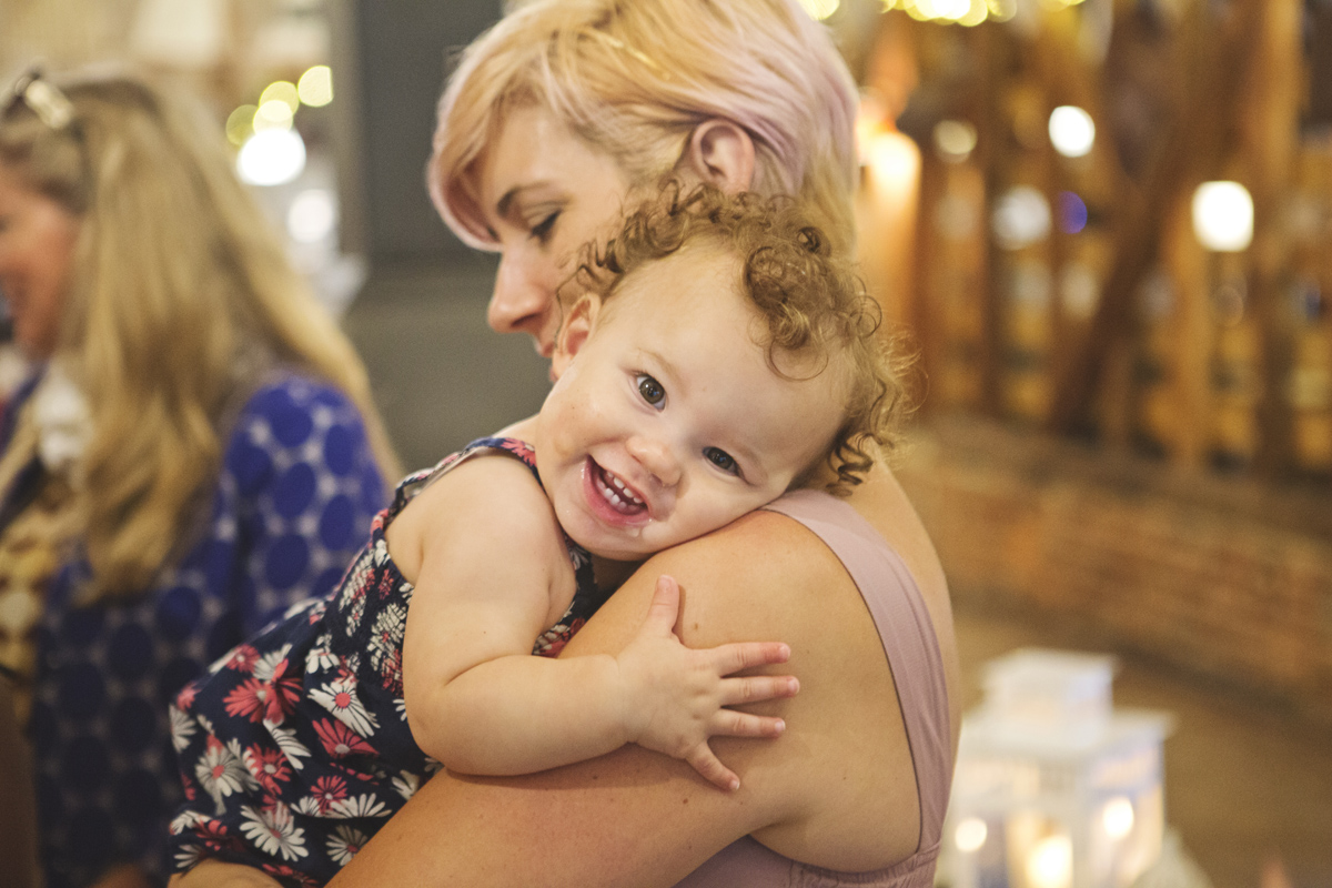 A toddler hugs her mother at a wedding reception