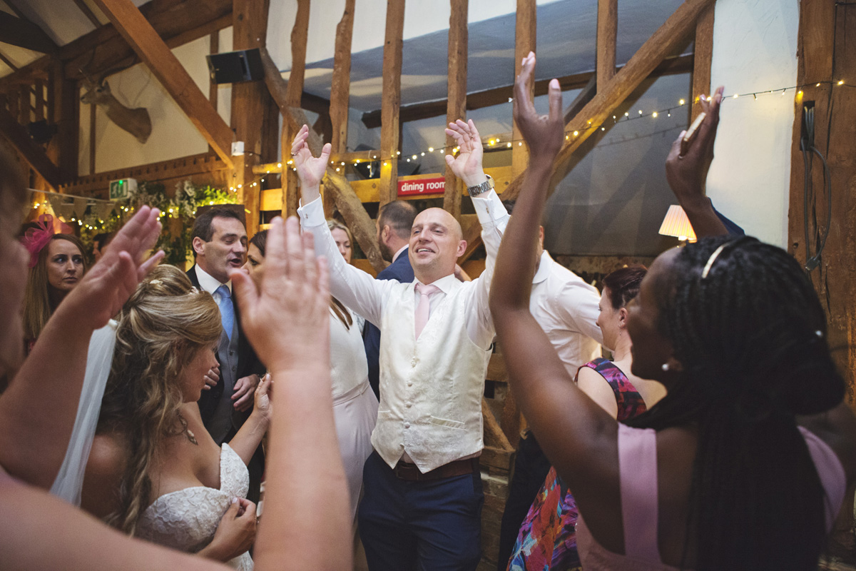 A groom and guests dance at the wedding reception at Red Barn in Surrey