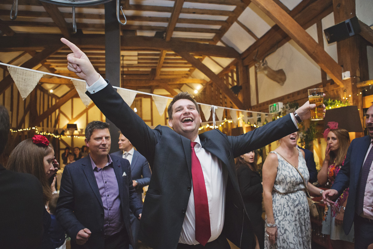 A wedding guest strikes a dance pose at a barn wedding reception