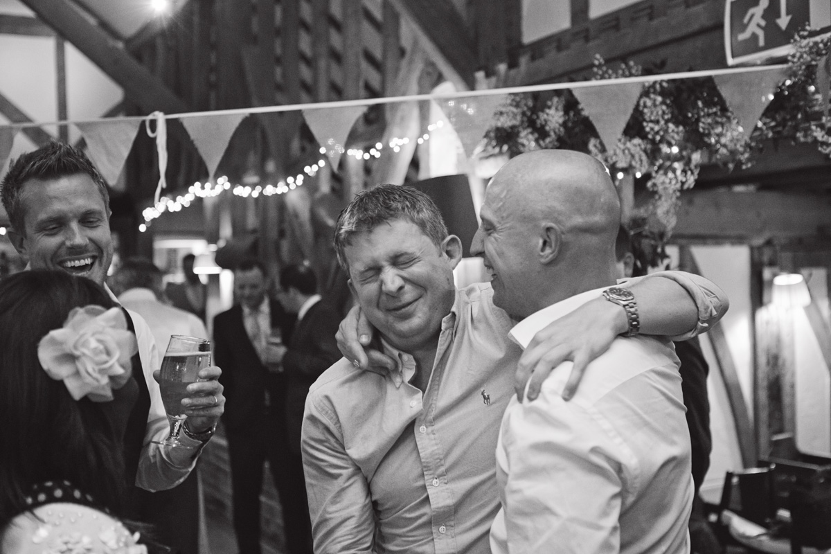 A Groom shares a joke while hugging one of his friends at a wedding