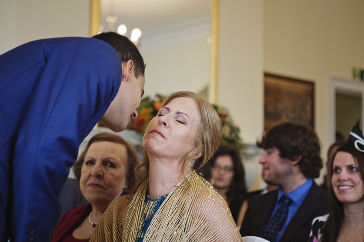 A Groom leans over to kiss his mother just before his marriage ceremony