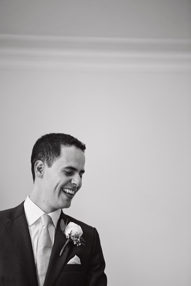 A black & white image of a groom laughing while he waits for his bride at a wedding
