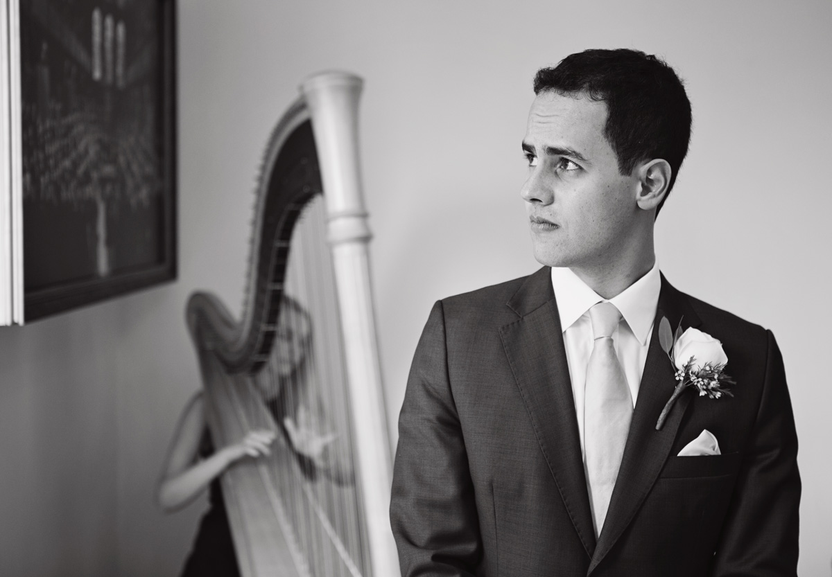 A mono image of a Groom waiting at the alter while a harpist plays in the background