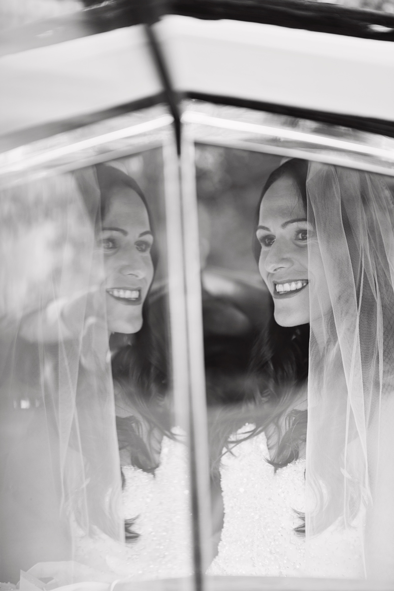 A smiling bride is reflected in the window of her wedding car as she arrives at her wedding
