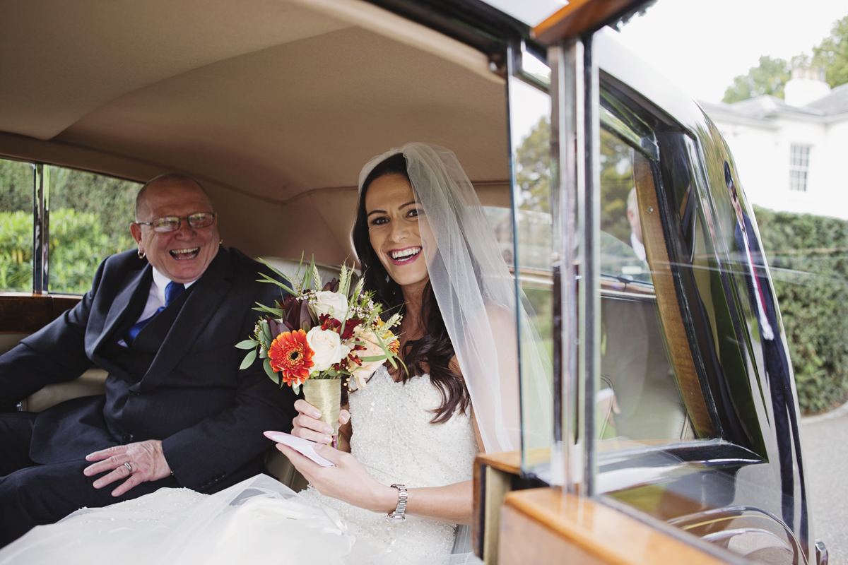 A bride & her father laugh in a wedding car as they arrive for her wedding